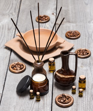 Aromatherapy and skincare accessories: open jar of cream, small glass vials of aromatic essential oils, crock, incense sticks, bamboo plate with water and coffee beans on old wooden planks 스톡 콘텐츠