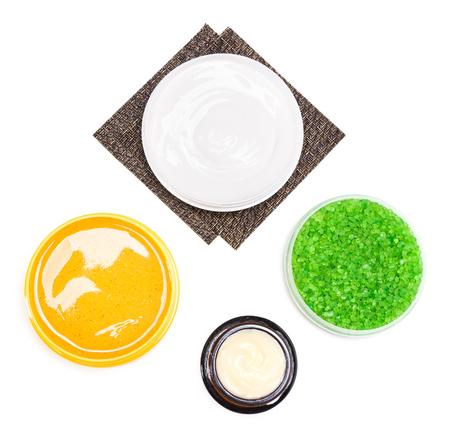 mimos: el cuidado del cuerpo productos cosm�ticos: ba�o de sal de mar, tarros llenos de cremas y exfoliante corporal natural sobre fondo blanco, vista desde arriba. Spa y de cuidado del cuerpo cosm�ticos