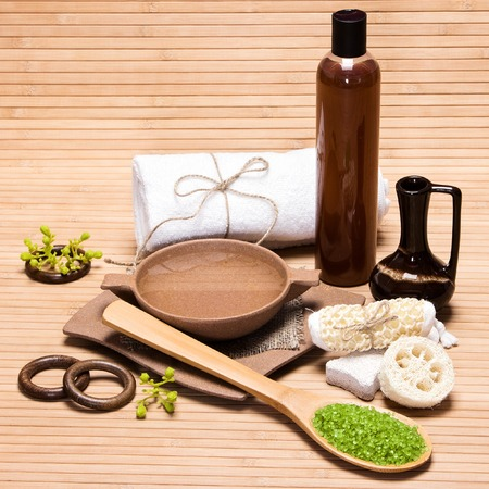 bath salt: Spa and pampering products and accessories: sea salt, pumice, loofah, wisp of bast, bamboo plate with water, crock, shower gel, bath towel on wooden surface