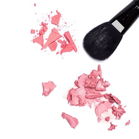 smeared: Different types of blushes. Close-up of crushed compact and smeared cream blushes with black makeup brush on white background