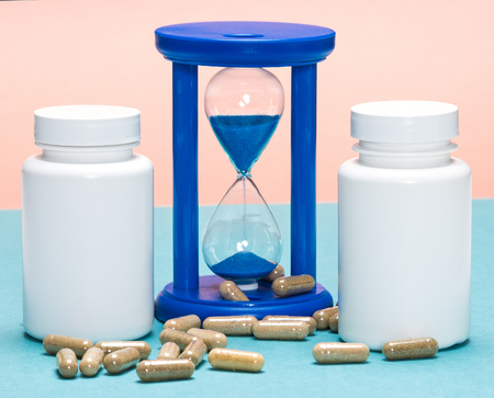 longevity drugs: Scattered capsules with white plastic jars and hourglass. Anti-aging supplements concept. Youth extension. Time and health Stock Photo