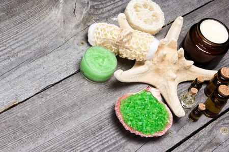 scrubbers: Spa and pampering products and accessories background. Sea salt in shell, body scrubbers, skin care cream, natural honey and lemongrass scrub, essential oils on old wooden planks. Copy space
