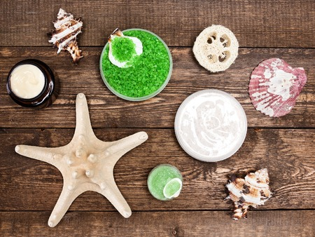 nut shell: Spa cosmetics and accessories: sea salt, loofah, skin care cream, natural creamy nut shell powder and sugar scrubs with conches and starfish on wooden planks. Top view Stock Photo