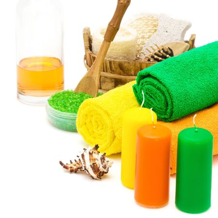 with orange and white body: Set of bright spa accessories in green, orange, yellow colors on white background. Towels, candles, shell, sea salt, shower gel and wooden basket with loofah, massage comb, pumice, body scrubber