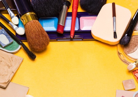 semicircular: Different makeup cosmetics and accessories laid out as semicircular frame. Bright yellow background. Copy space Stock Photo