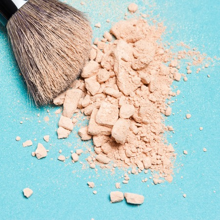 matte: Close-up of makeup brush with crushed mineral matte compact powder on blue surface. Square crop Stock Photo