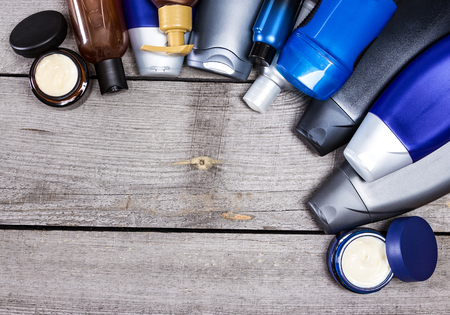 shampoo: Mens cosmetics background. Various cosmetic products for men laid out as semicircular frame on old wooden planks. Copy space