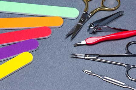 Various manicure tools on gray textured background. Nail clippers, nail and cuticle scissors, colored nail files, double ended cuticle trimmer  pusher, cuticle remover
