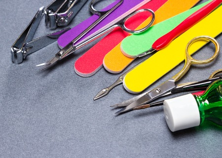 Various manicure tools on gray textured surface. Nail clippers, nail and cuticle scissors, colored nail files, double ended cuticle trimmer / pusher, cuticle remover, nail art brushes and nail oil Banque d'images