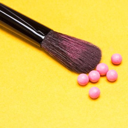 cosmeticos: Primer plano de la brocha de maquillaje con las bolas de rubor brillo de color rosa sobre fondo amarillo