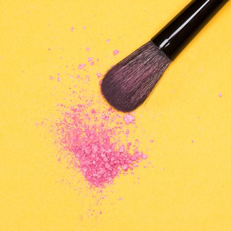 cosmeticos: Primer plano de la brocha de maquillaje con brillo picado de color rubor rosa sobre fondo amarillo Foto de archivo