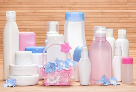 cremas faciales: Diferentes productos cosméticos para el cuidado de la piel en la superficie de madera. Diversos limpiadores faciales, removedores de maquillaje, de día y de noche cremas, desodorante antitranspirante con linda cesta de mimbre y pequeñas flores