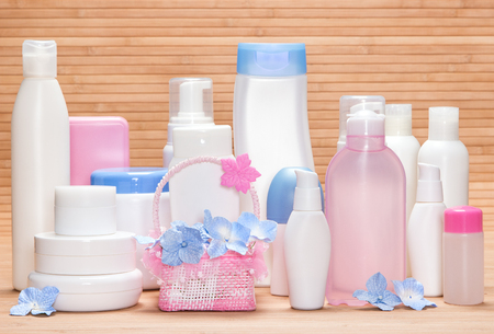 aging skin: Different cosmetic products for skincare on wooden surface. Various facial cleansers, makeup removers, day and night creams, antiperspirant deodorant with cute wicker basket and little flowers