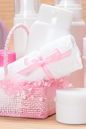 aging skin: Accessories and cosmetics for skin care. Close-up of white towel tied with satin ribbon with bow in small cute wicker basket surrounded by various cosmetic products for skincare on wooden surface