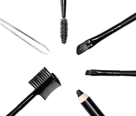 Accessories for care of the brows: eyebrow pencil, angle brushes made from natural bristles, spooly brush tweezers and brow comb / brush combo on white background. Eyebrow grooming tools