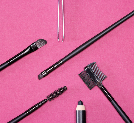 Accessories for care of the brows: eyebrow pencil, angle brushes made from natural bristles, spooly brush, tweezers and brow comb / brush combo on bright claret background. Eyebrow grooming tools 스톡 콘텐츠