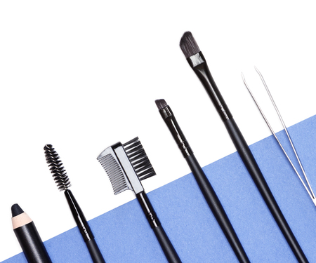 bristles: Accessories for care of the brows: eyebrow pencil, angle brushes made from natural bristles, spooly brush, tweezers and brow comb  brush combo on white and blue background. Eyebrow grooming tools