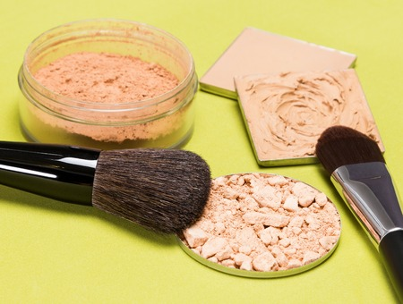 loose skin: Set of makeup products to even out skin tone and complexion: crushed compact powder, concealer, correcting powder, jar of loose cosmetic powder with makeup brushes on herbal green textured surface