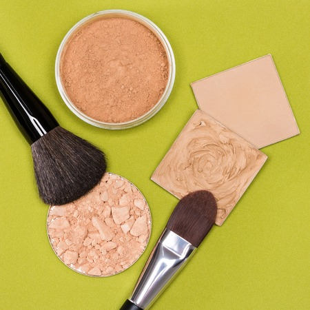 flaws: Set of makeup products to even out skin tone and complexion: concealer, correcting powder, jar of loose cosmetic powder, crushed compact powder with makeup brushes on herbal green textured surface