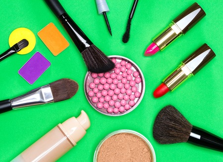 colored bottle: Various makeup products on green background: jar with shimmer blush balls surrounded by cream foundation bottle, jar of loose powder, lipstick, mascara, liquid eyeliner, colored eyeshadow and brushes