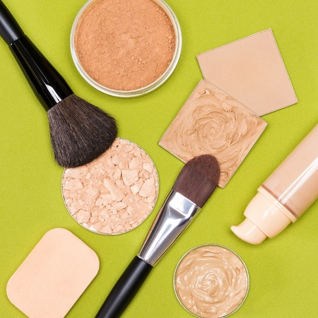 flaws: Close-up of concealer, correcting powder, liquid foundation near of its open bottle, jar of loose powder, crushed compact powder, makeup brushes and cosmetic sponge on herbal green textured surface
