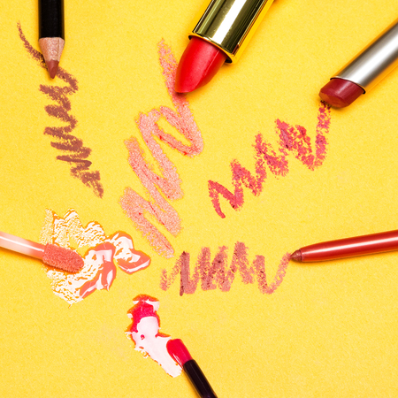 glosses: Different lip makeup cosmetics: lip liners, lip glosses and lipstick on yellow background
