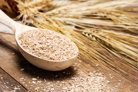 Close-up of wooden spoon filled with wheat bran on the background of wheat ears. Dietary supplement to improve digestion. Source of dietary fiber. Wooden planks background. Shallow depth of field Standard-Bild