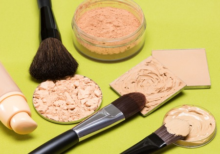 loose skin: Makeup products to even skin tone and complexion: concealer, correcting powder, liquid foundation, its open bottle, crushed compact powder, jar of loose powder, makeup brushes. Focus on central brush Stock Photo