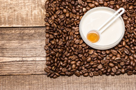 busting: Cellulite busting product concept. Anti-cellulite cosmetics with caffeine. Jar of cream with a spoon of coffee essential oil surrounded by coffee beans on wooden planks. Top view. Copy space Stock Photo