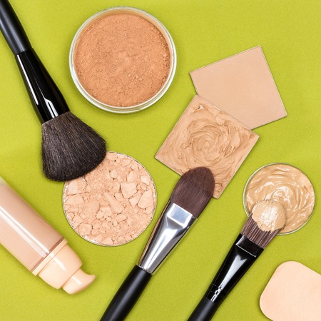 loose skin: Makeup products to even out skin tone and complexion: concealer, correcting powder, liquid foundation, its open bottle, jar of loose powder, crushed compact powder, makeup brushes, cosmetic sponge Stock Photo