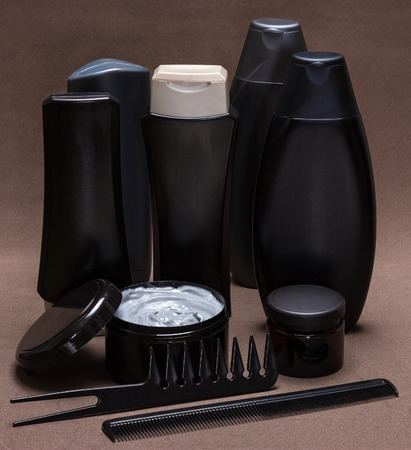 Hair care and styling products and accessories. Black and gray cosmetic containers, extra wide tooth and fine-tooth combs on brown textured surface