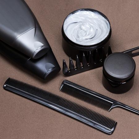 Différents produits de coiffure et accessoires pour créer belle coiffure. Cosmétiques et divers types de peignes sur surface texturée marron