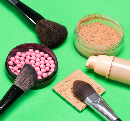 loose skin: Basic makeup products to create a beautiful skin tone and complexion: cream and liquid foundation, loose cosmetic powder and blush with makeup brushes on green background Stock Photo