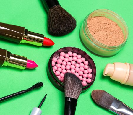 unusual angle: Various makeup products: jar with shimmer blush balls surrounded by cream foundation bottle, jar of loose powder, lipstick, mascara, liquid eyeliner, brushes. Unusual angle