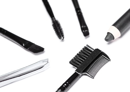 Accessories for care of the brows. Brow comb / brush combo surrounded by other eyebrow grooming tools: tweezers, angle brushes, spooly brush, eyebrow pencil on white background. Shallow depth of field