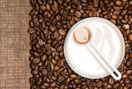 busting: Cellulite busting product concept. Anti-cellulite cosmetics with caffeine. Jar of cream with a spoon of coffee essential oil surrounded by coffee beans on wooden surface. Top view. Copy space