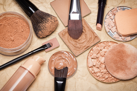even: Various makeup products to even out skin tone and complexion on aged paper. Foundation, loose and compact powders, concealer pencil, corrector with brushes and cosmetic sponges. Retro style processing Stock Photo