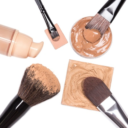 complexion: Basic makeup products to create beautiful skin tone and complexion. Corrector, foundation, powder with brushes on white background Stock Photo