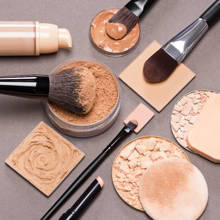 Close-up of liquid foundation, loose and compact powders, concealer pencil, correctors with brushes and cosmetic sponges on brown textured surface. Makeup products to even out skin tone and complexion Standard-Bild