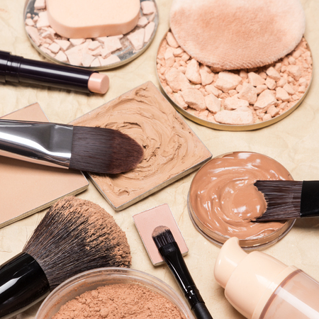 loose skin: Makeup brushes with loose and correcting cosmetic powders surrounded by other makeup products to even out skin tone and complexion on crumpled aged paper. Shallow depth of field