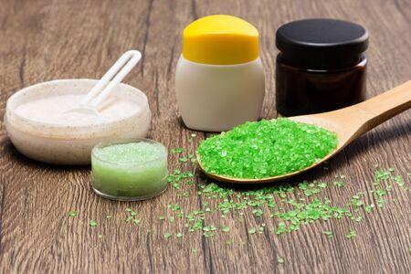 mimos: Primer plano de la cuchara de madera llena de sal marina gruesa, exfoliantes naturales verdes y cremas para el cuidado de la piel en la superficie de madera. Spa y de cuidado del cuerpo productos. Muy poca profundidad de campo
