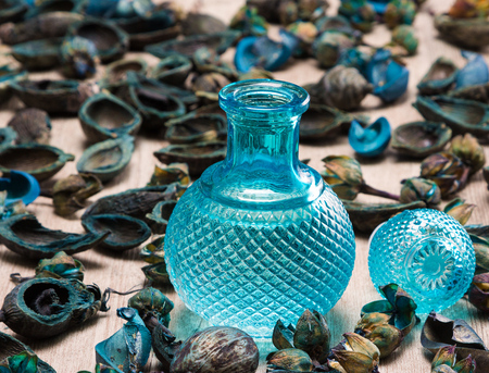 attar: Close-up of filled blue glass bottle surrounded by dried plants on wooden surface. Cool fragrance concept