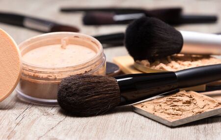 flaws: Different types of makeup cosmetic products to even out skin tone and complexion with brushes on wooden surface. Close-up, shallow depth of field