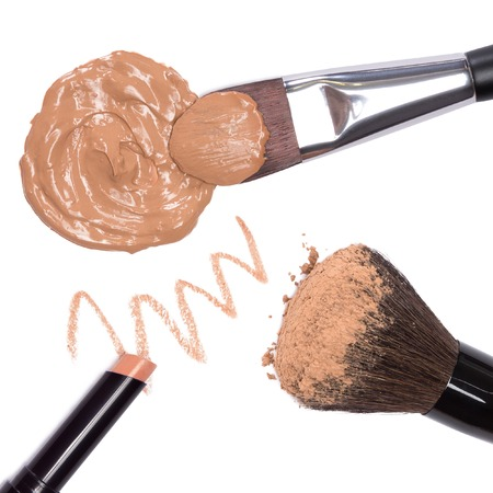loose skin: Basic makeup products to create beautiful skin tone and complexion. Concealer pencil, foundation, loose powder with brushes. Close-up on white background