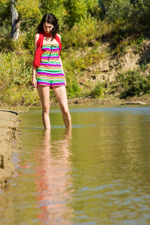 head down: Young beautiful slender woman with her head down stands in the water near the sandy shore of the river. Mysterious pretty girl wanders in the shallow waters Stock Photo