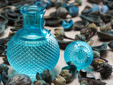 dulcet: Close-up of filled blue glass bottle surrounded by dried plants on wooden surface. Cool fragrance concept