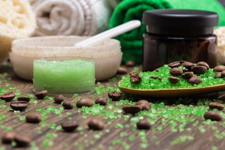 Anti-cellulite cosmetics with caffeine. Wooden spoon with sea salt and coffee beans, natural body scrubs, skin care cream, towels, loofah. Spa and cellulite busting products. Shallow depth of field