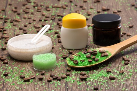 creams: Anti-cellulite cosmetics with caffeine. Close-up of wooden spoon filled with green coarse sea salt and coffee beans, natural body scrubs and skin care creams on wooden surface. Shallow depth of field
