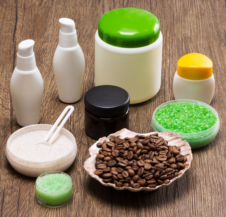 busting: Spa and cellulite busting products. Shell filled with coffee beans, natural scrubs, sea salt, skin care creams on wooden surface. Anti-cellulite cosmetics with caffeine