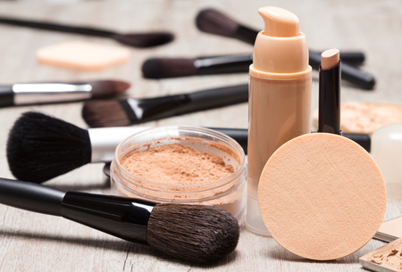 Makeup products and accessories to even out skin tone and complexion. Round cosmetic sponge, bottle of liquid foundation, concealer pencil, jar of loose powder, makeup brushes on shabby wooden surface Фото со стока